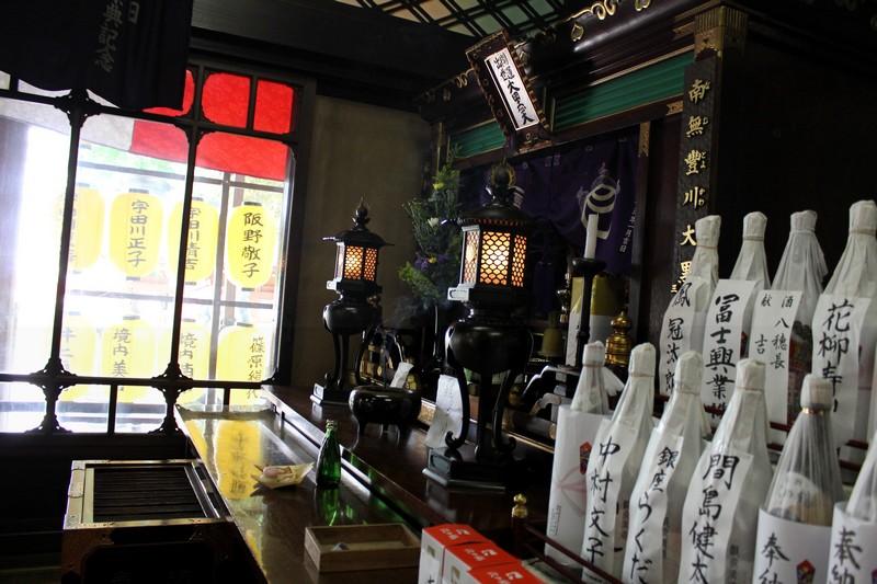 Sake offering at an indoor shrine.